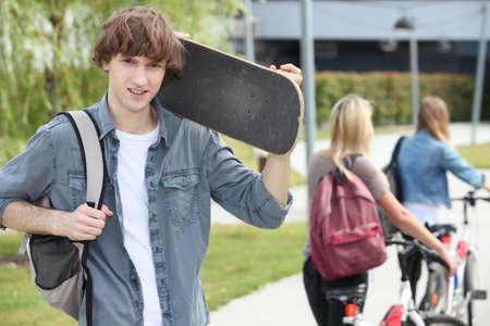 back packs: Student on campus with a skateboard Stock Photo