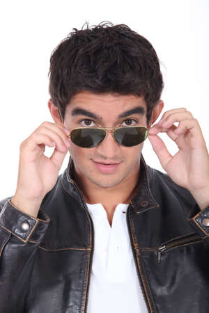 Young man wearing leather jacket and trendy sunglasses photo