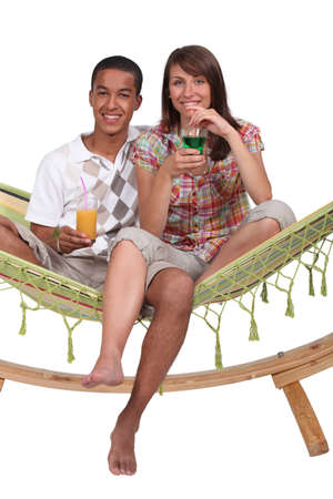 Couple sat on hammock with cocktails photo