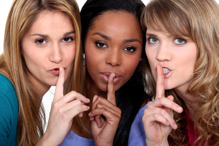 Three women with the fingers to their lips photo