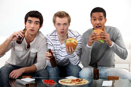 Male friends eating burgers and watching sport on TV photo