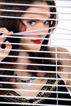ventanas abiertas: Mujer atractiva que mira a escondidas a trav�s de algunas persianas Foto de archivo
