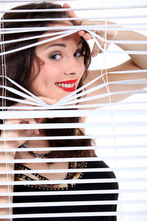 come hither: sexy woman looking through the blinds