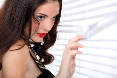 looking through window: Woman spying through the blinds