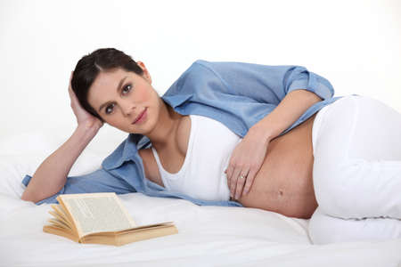 Pregnant woman reading to pass the time photo