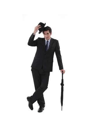 estereotipo: Hombre de negocios con un sombrero y paraguas