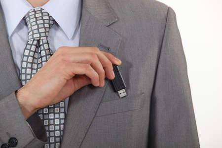pocket pc: businessman putting a flash drive in his pocket