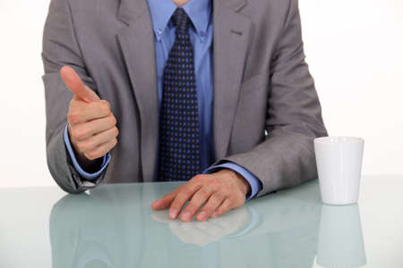 thumbup: A cropped picture of a businessman giving the thumb up.