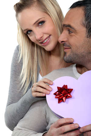 a woman giving a heart shaped box to her husband photo