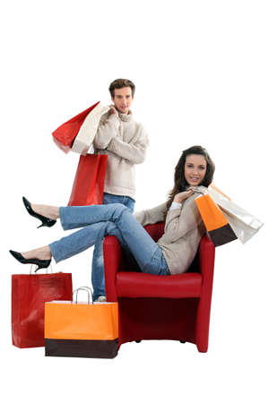 Woman sitting in a chair and surrounded by shopping bags photo
