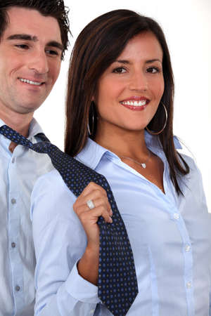 dominating: A businesswoman pulling her colleague by the tie.