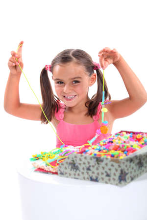 Girl making a bead necklace photo