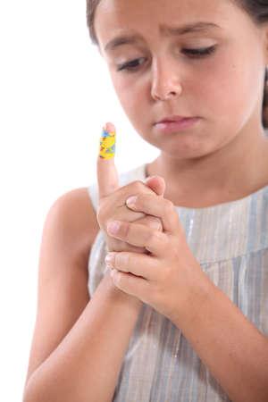 niños vistiendose: niña mirando un vendaje en el dedo Foto de archivo