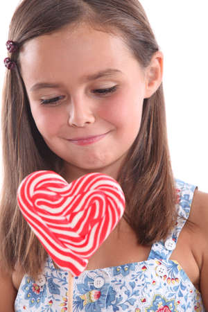 Little girl with heart-shaped lollipop photo