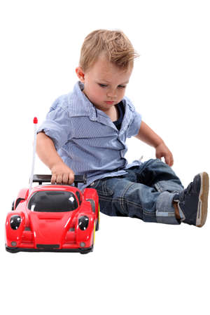 Young boy playing with a toy car Stock Photo
