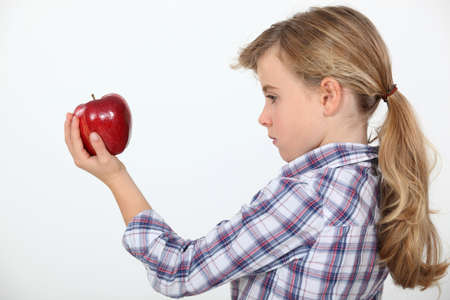disdain: Girl holding an apple Stock Photo