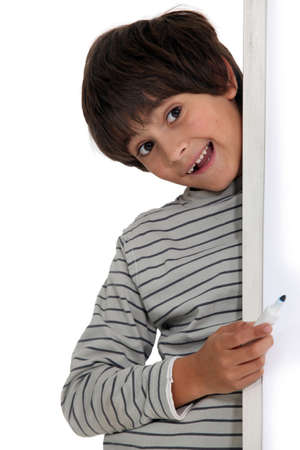 7 years old: Little boy hiding in studio Stock Photo