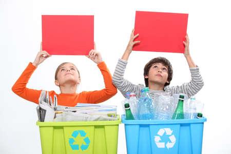 niños reciclando: Los niños que sostienen tarjetas rojas en blanco por encima de su reciclaje