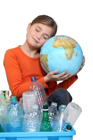 Little girl holding globe and recycling bottles Stock Photo