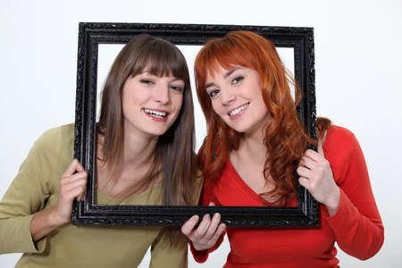 poking: Women poking heads through empty picture frame Stock Photo