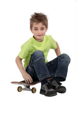 boy skater: A kid sitting on his skateboard. Stock Photo