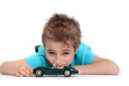 spare car: Young boy playing with a toy car Stock Photo