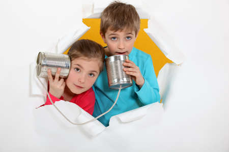 Brother and sister speaking into tin can photo