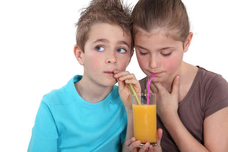 dehydrated: Children drinking a glass of orange juice Stock Photo