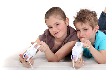 video games: Brother and sister playing video games Stock Photo