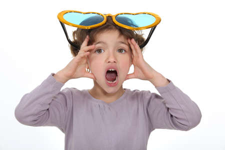 big mouth: Shocked little girl wearing comedy glasses