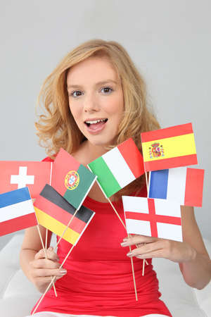 fair haired: Fair haired woman with a variety of European flags Stock Photo