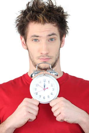 wimp: young guy with swollen eyes showing alarm clock Stock Photo
