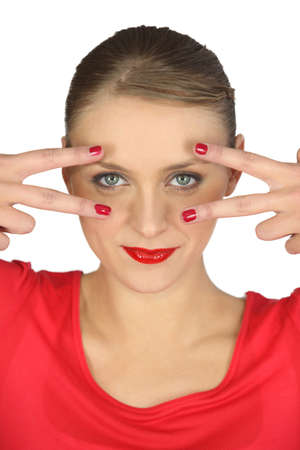 spread around: Woman holding her fingers around her eyes Stock Photo