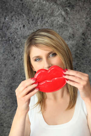 Blond woman holding novelty lips in  front of her face photo