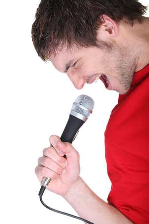 persona cantando: Hombre cantar en el micrófono Foto de archivo