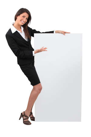 Portrait of woman in skirt suit with blank board photo