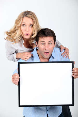 Surprised couple holding blank message board photo