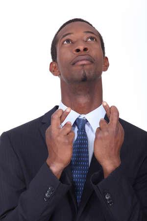 Man in een pak kruising zijn vingers voor geluk Stockfoto