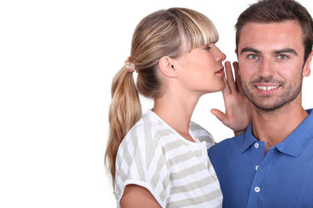 shh: Young woman whispering into her boyfriend