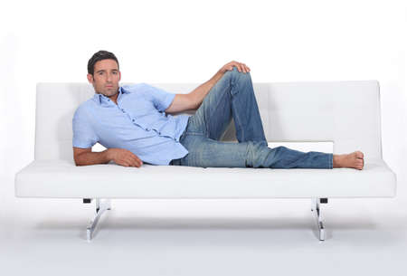 grouch: Sulky man lying on a couch Stock Photo