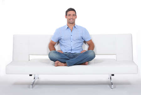 Young man sitting on white sofa photo