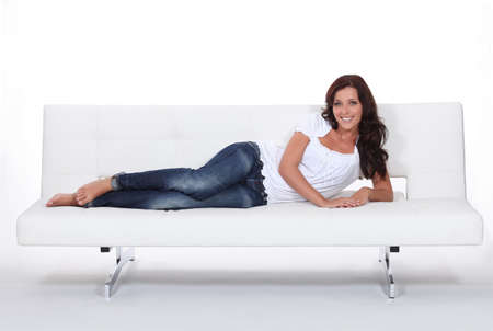 Brunette laid on designer sofa photo