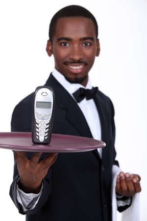 Waiter with a cellphone on a tray photo