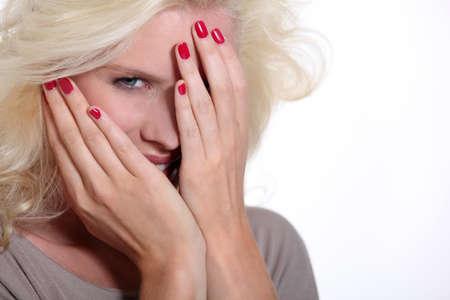 mischief: pretty blonde hiding her face Stock Photo