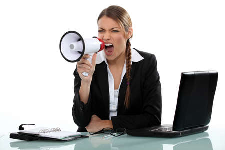 businesswoman shouting angrily with loudspeaker and laptop photo