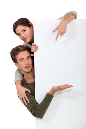 arms around: Man and woman pointing to a blank board Stock Photo