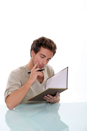 Pensive man writing in book photo