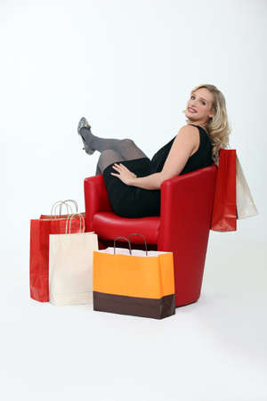 rebates: Woman sitting in red chair surrounded by bags Stock Photo