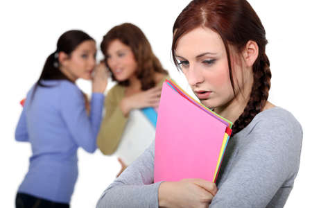 Lonely young woman being gossiped about by others photo