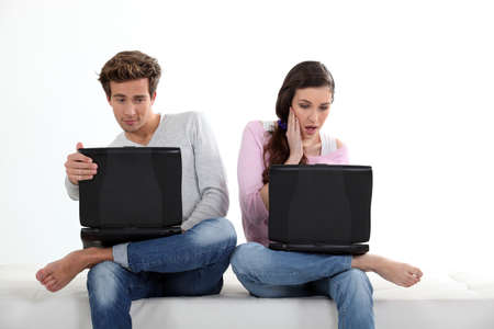 Young couple with their laptops photo